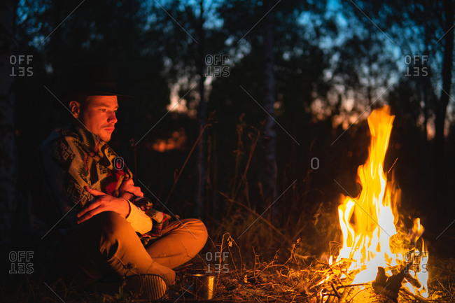 Man wearing poncho sits by the fire in the forest in dusk