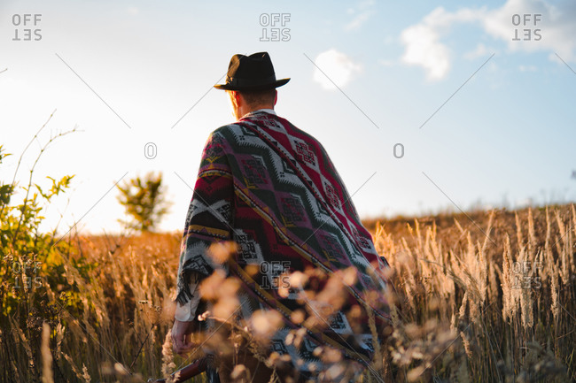 Man in poncho in a country field, atmospheric rural scene
