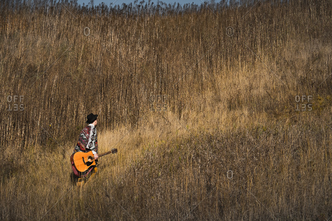Country musician with acoustic guitar walks in grasses at a field