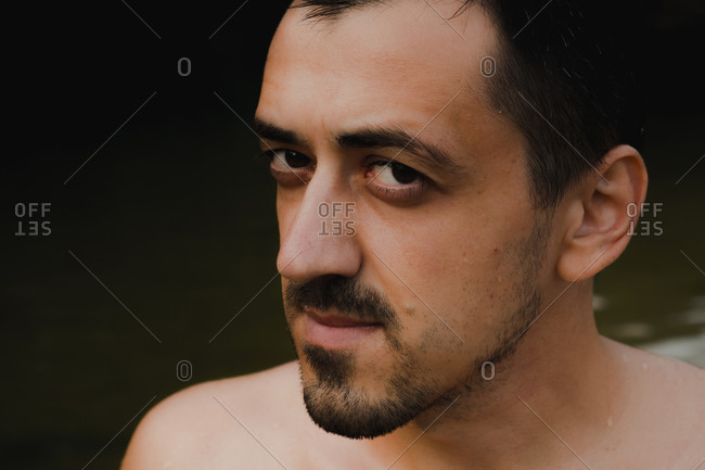 Portrait of a young male person with bristle with wet skin