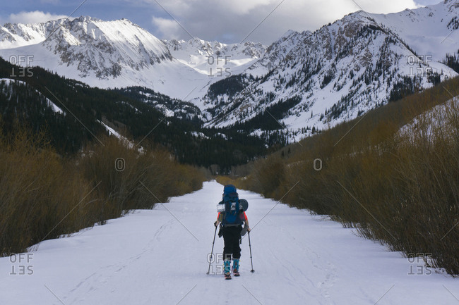 Rear view of hiker splitboarding on snow covered land against mountains