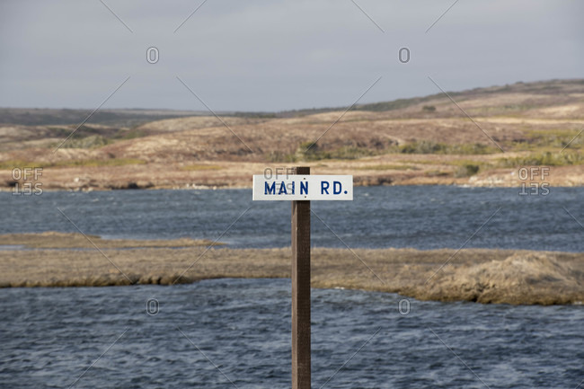 Text on sign board against river