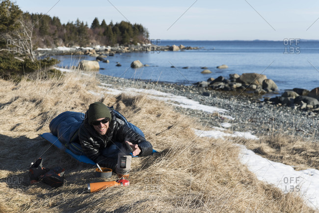 Male hiker preparing food while lying in sleeping bag on field by sea