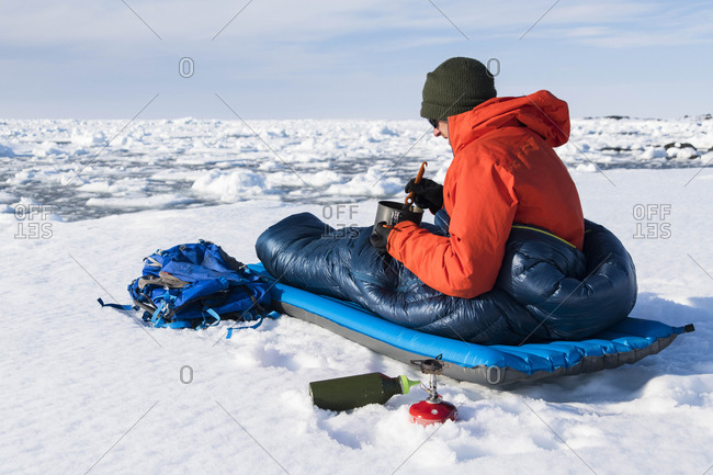 Male hiker having food while sitting in sleeping bag on snow covered mountain