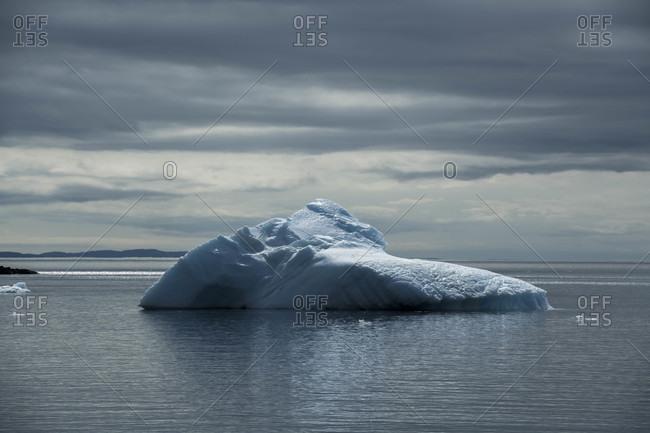 Iceberg in ocean against cloudy sky