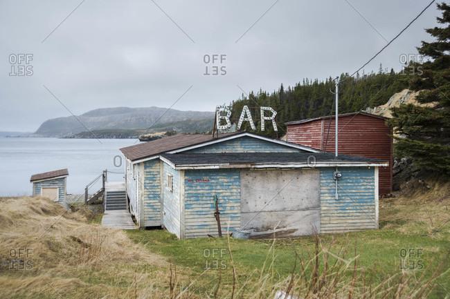 Old bar on mountain against sky along ocean in Newfoundland