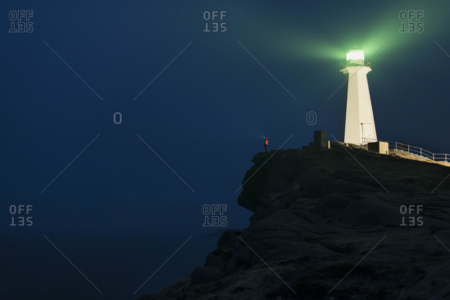 Low angle view of Illuminated lighthouse on mountain against sky at night