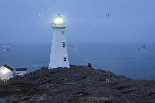Illuminated lighthouse on mountain against sky at dusk