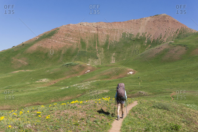 Rear view of woman hiking on mountain during vacation