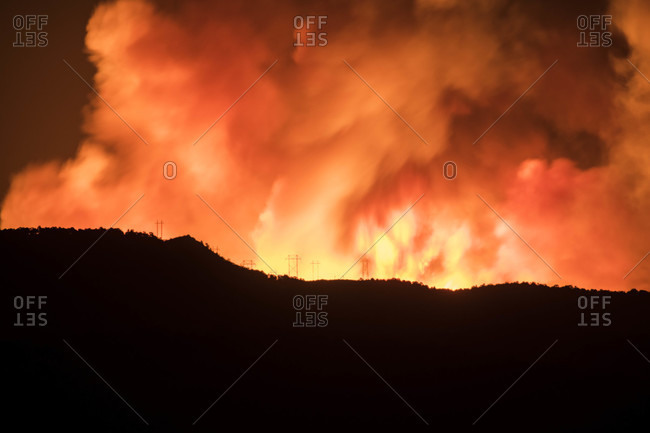Silhouette mountain with wildfire in background at night