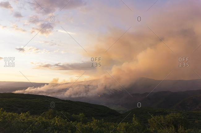 Smoke emitting from wildfire on mountain against sky
