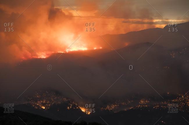 Smoke emitting from forest burning during sunset