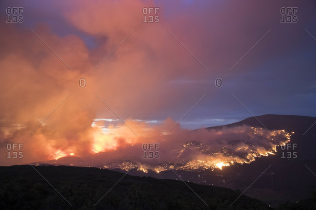 Smoke emitting from wildfire on mountain against sky at dusk