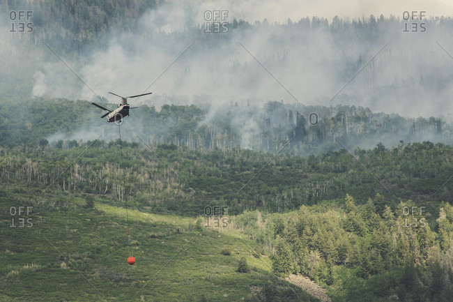 Basalt, CO, United States - July 12, 2018: Helicopter flying with fire retardant while smoke emits from wildfire in forest