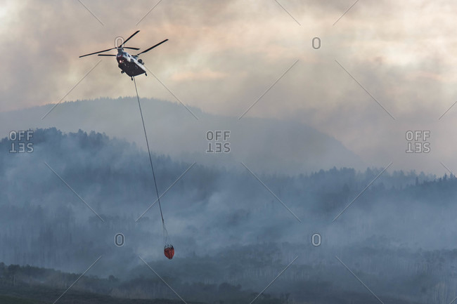 Military helicopter flying with fire retardant while smoke emitting from wildfire during sunset