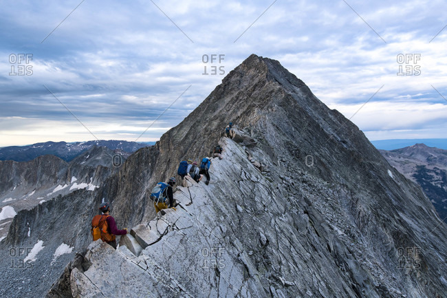 Male and female hikers climbing mountain peak against cloudy sky