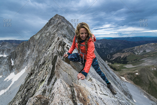 Smiling female hiker climbing Capitol Peak against sky