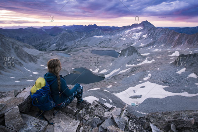 Female hiker looking at mountains while sitting on rocks during sunset