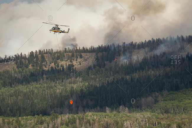 Basalt, CO, United States - July 19, 2018: Military helicopter flying with fire retardant while smoke emits from forest