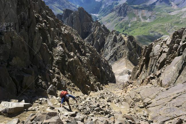 Male hiker climbing mountain during summer