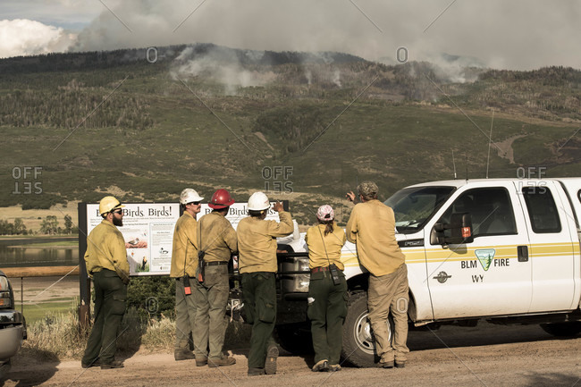 Basalt, CO, United States - July 19, 2018: Firefighters discussing while smoke emits from wildfire