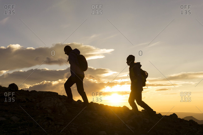 Silhouette female hikers on mountain against sky during sunrise