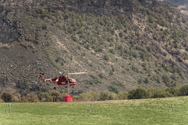 Basalt, CO, United States - July 27, 2018: Military helicopter with fire retardant against mountain