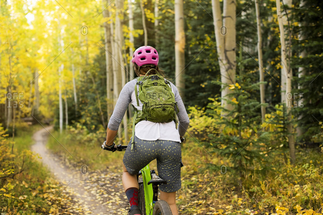 Rear view of young woman mountain biking in forest during autumn