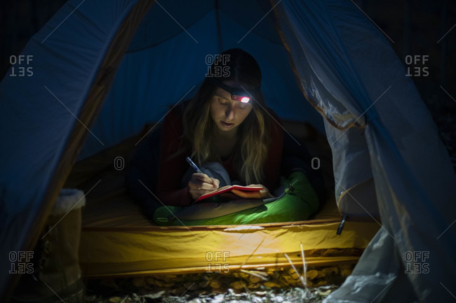 Young woman writing in diary in tent at night