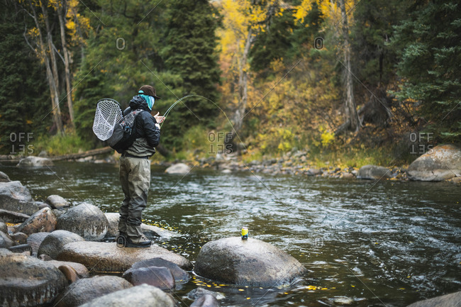 Man fly fishing while standing on rock at Roaring Fork River