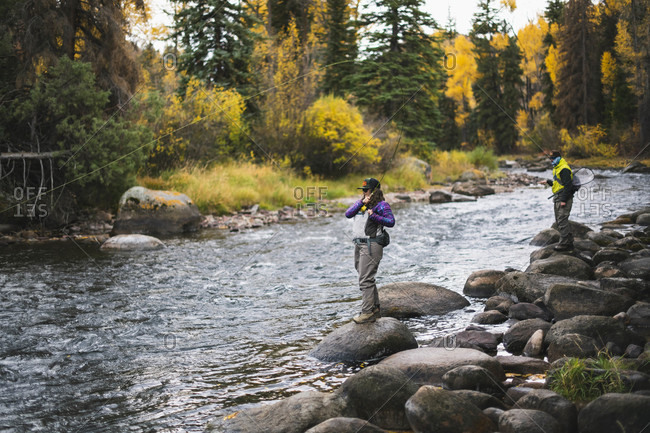 Man and woman fly fishing while standing on rocks at Roaring Fork River