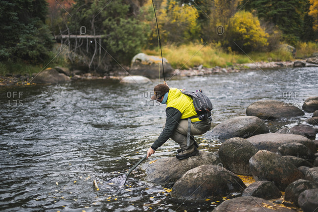 Side view of man fly fishing at Roaring Fork River during autumn