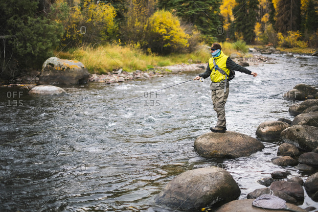 Man fly fishing while standing on rock at Roaring Fork River during autumn