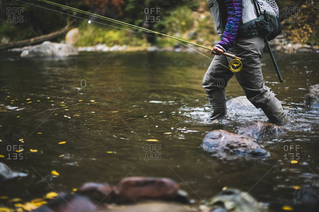 Midsection of woman fly fishing at Roaring Fork River during autumn