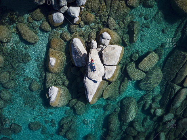 Drone shot of woman relaxing on rock at Lake Tahoe on sunny day