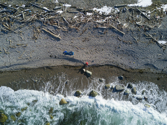 Drone shot of hiker at sea shore during winter