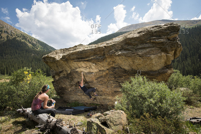 Woman looking at female friend bouldering on rock