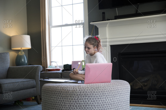 Young Girl Works on Laptop Computer Sitting on Living Room Ottoman
