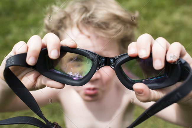 Out of Focus Little Boy Looks Through In Focus Pair of Goggles