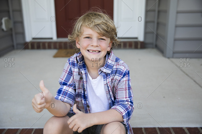 Toothless First Grade Boy Gives Thumbs Up While Sitting on Brick Steps