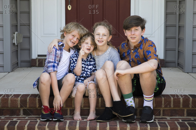 Four Siblings Sit Together on Brick Front Steps in Mismatched Outfits