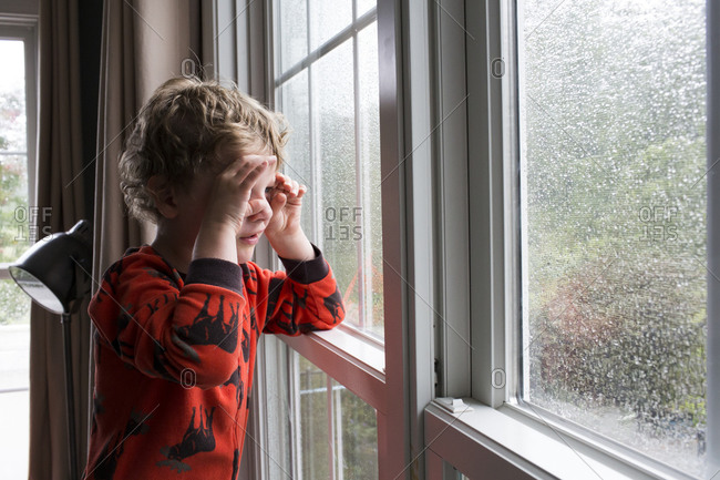 Young Boy Looks Through Rain Covered Window With Pretend Binoculars