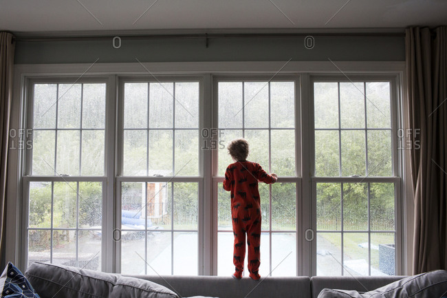 Small Boy Looks Out Large Living Room Window at Rainy Back Yard