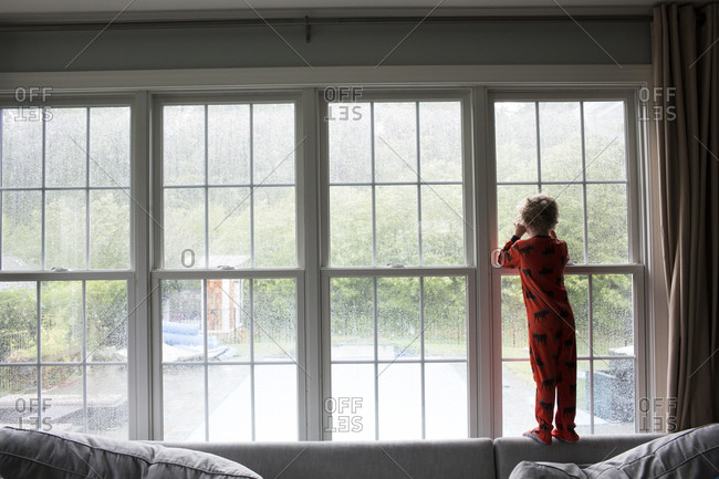 Wide Rear View of Boy in Red Pajamas Looking Out Window at Rain