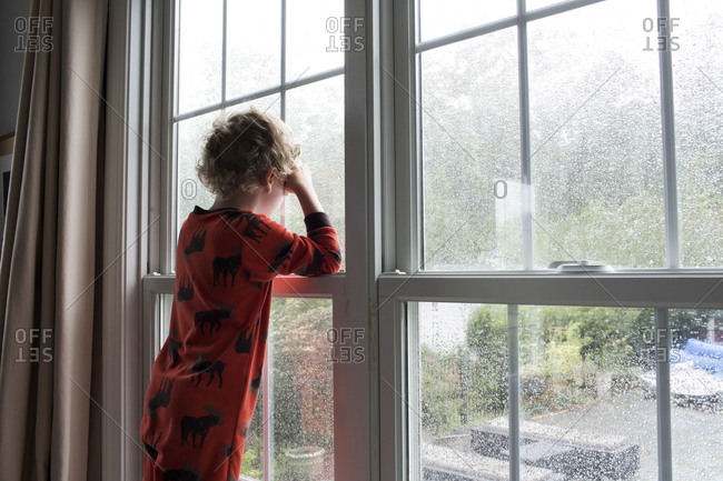Rear View of Young Boy With Curly Hair Looking Out Rain Covered Window