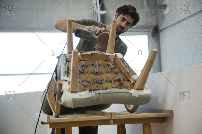 Low angle view of a man repairing and restoring an old chair