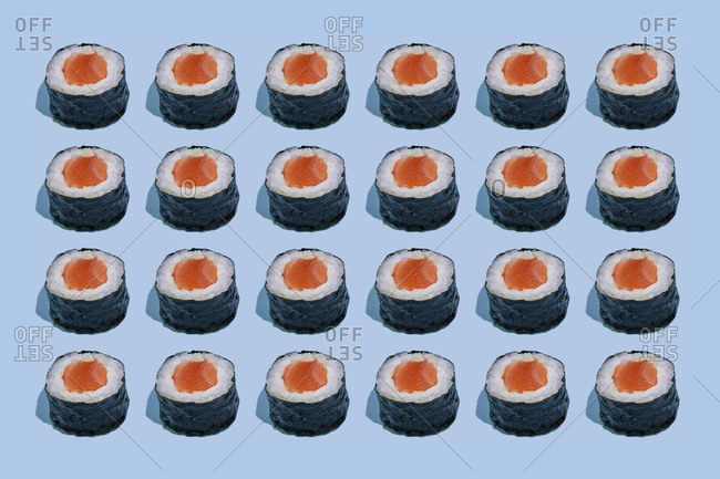 Salmond sushi makis pattern on blue background with shadows