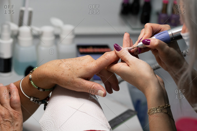 Senior woman in cosmetic salon doing manicure with specialist
