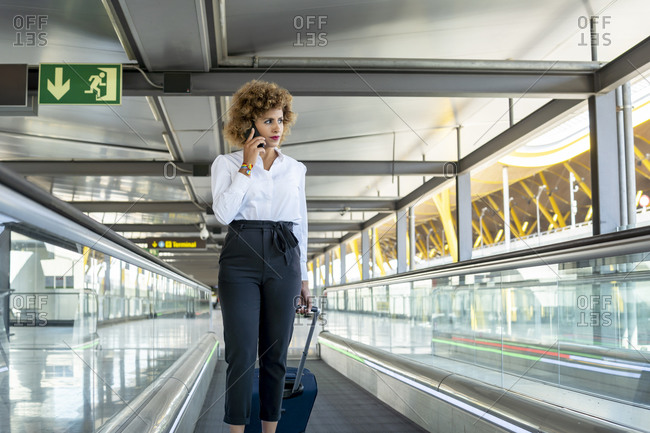 Stewardess with her suitcase talking from her smartphone