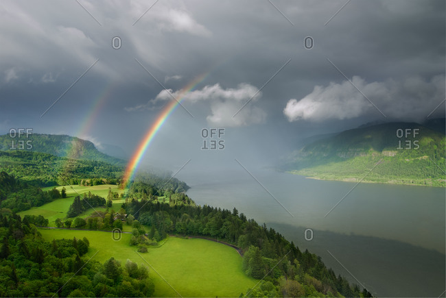 Beautiful double rainbow in lush river gorge, with pasture and forest